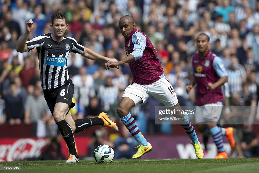 Fabian Delph of Aston Villa is challenged by Mike Williamson of Newcastle United during the Barclays Premier League match between Aston Villa and Newcastle United at Villa Park on August 23, 2014 in Birmingham, England.