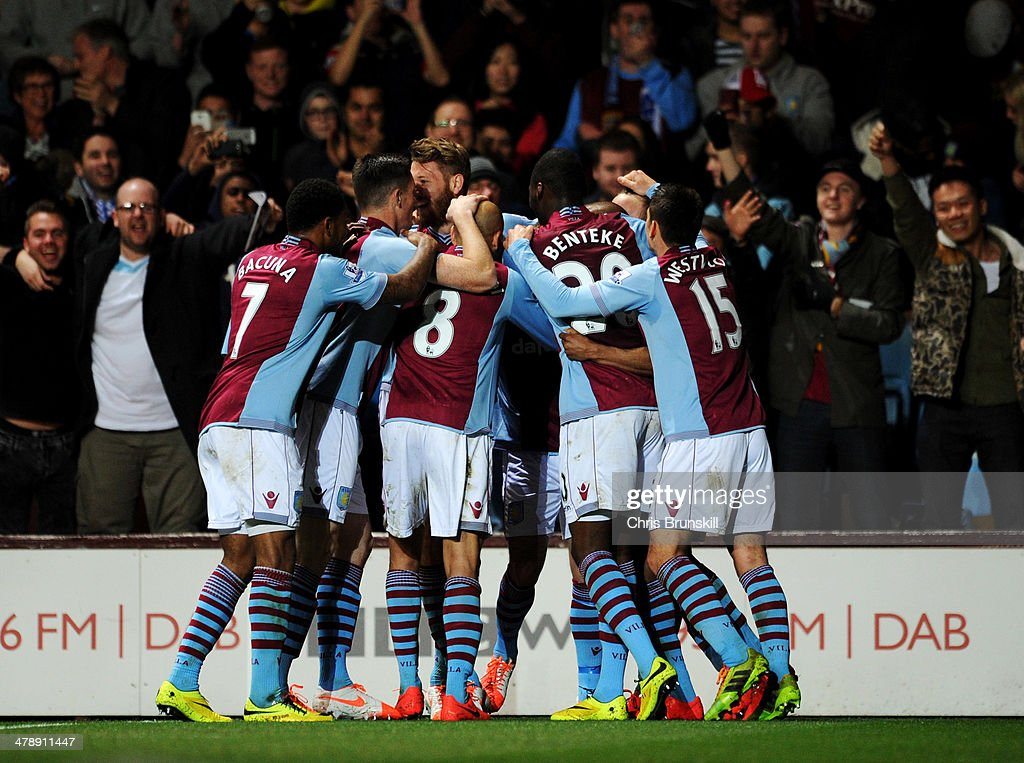 Fabian Delph of Aston Villa (obscured) is congratulated by team mates as he scores their first goal during the Barclays Premier League match between Aston Villa and Chelsea at Villa Park on March 15, 2014 in Birmingham, England.