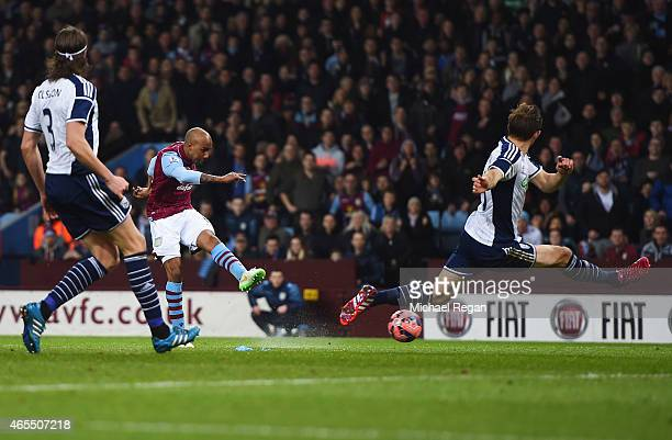 Fabian Delph of Aston Villa shoots past Craig Dawson of West Bromwich Albion to score their first goal during the FA Cup Quarter Final match between...