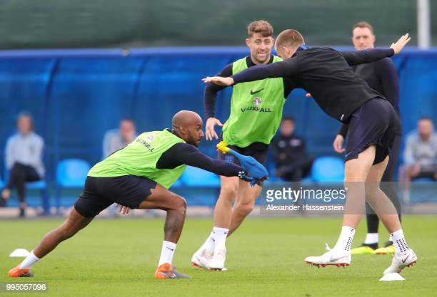 Fabian Delph of England attempts to tag Eric Dier of England with a toy chicken during the England training session on July 10 2018 in Saint...
