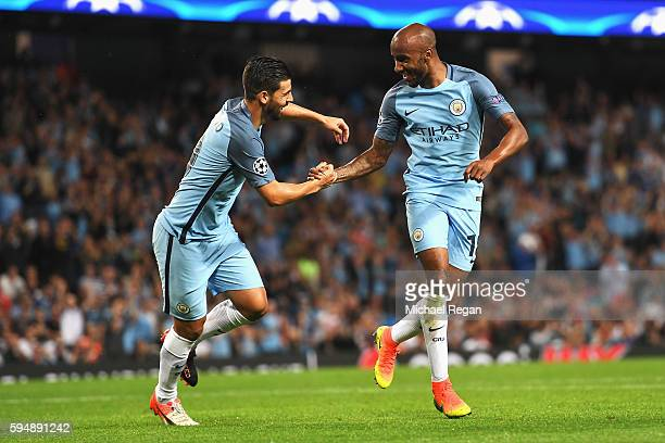 Fabian Delph of Manchester City celebrates scoring the opening goal with Nolito during the UEFA Champions League Playoff Second Leg match between...
