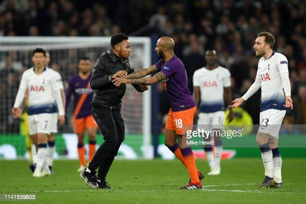 Fabian Delph of Manchester City confronts a pitch invader as Christian Eriksen of Tottenham Hotspur reacts during the UEFA Champions League Quarter...