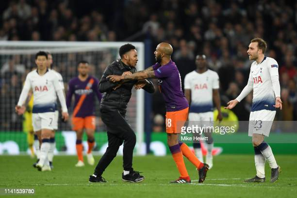 Fabian Delph of Manchester City confronts a pitch invader during the UEFA Champions League Quarter Final first leg match between Tottenham Hotspur...
