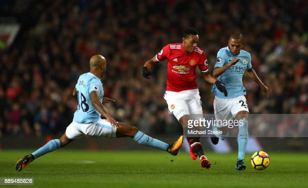 Fabian Delph of Manchester City lunges at Anthony Martial of Manchester United and Fernandinho of Manchester City during the Premier League match...
