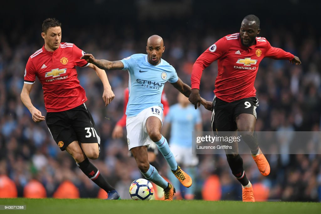 Fabian Delph of Manchester City runs with the ball under pressure from Nemanja Matic of Manchester United and Romelu Lukaku of Manchester United during the Premier League match between Manchester City and Manchester United at Etihad Stadium on April 7, 2018 in Manchester, England.