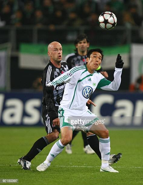 Fabian Ernst of Besiktas and Makoto Hasebe of Wolfsburg battle for the ball during the UEFA Champions League Group B match between VfL Wolfsburg and...