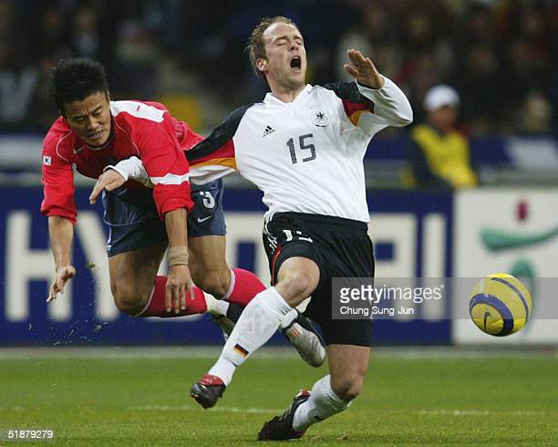 Fabian Ernst of Germany is brought down by Park Jae-Hong of South Korea during the International Friendly match at the Asiad Main Stadium on December...
