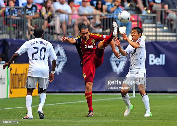 Fabian Espindola of Real Salt Lake gets his leg up high to kick the ball while Vancouver Whitecap players Dane Richards and teammate Lee YounPyo look...