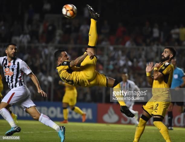 TOPSHOT Fabian Estoyanoff of Uruguay's Penarol kicks the ball next to Santiago Salcedo of Paraguay's Libertad during their 2018 Libertadores Cup...
