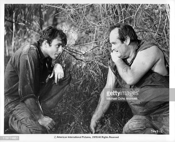 Fabian Forte huddles with fellow prisoner Bill Thurman in a scene from the film 'A Bullet For Pretty Boy' 1970