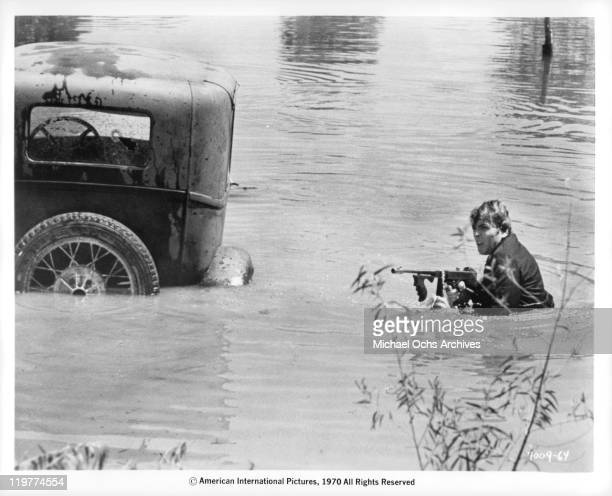 Fabian Forte tries to hold off police while walking to his sunken car in a scene from the film 'A Bullet For Pretty Boy' 1970