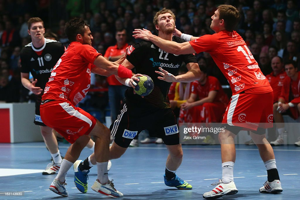 Fabian Gutbrod (C) of Germany is challenged by Michael Allendorf (L) and Christian Hildebrand of Melsungen during a benefit match between the German national handball team and MT Melsungen at Rothenbach-Halle on March 5, 2013 in Kassel, Germany.