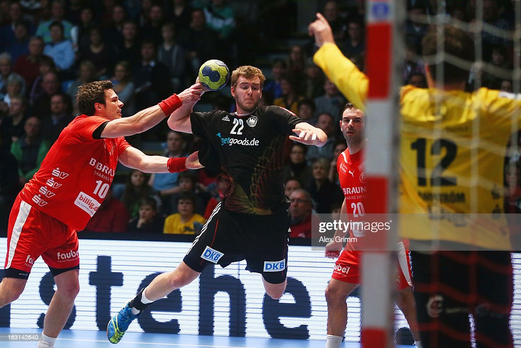 Fabian Gutbrod of Germany tries to score against Malte Schroeder, Savas Karipidis and goalkeeper Per Sandstroem (L-R) of Melsungen during a benefit match between the German national handball team and MT Melsungen at Rothenbach-Halle on March 5, 2013 in Kassel, Germany.