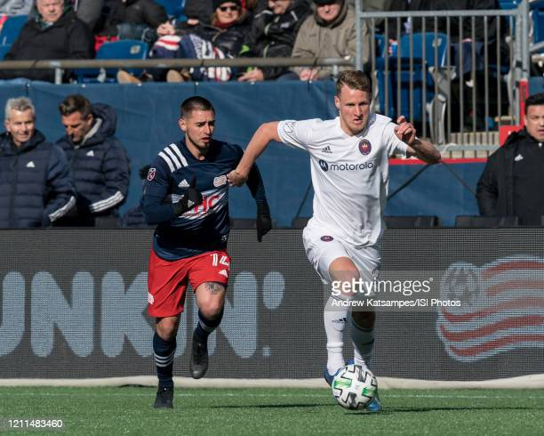 Fabian Herbers of Chicago Fire brings the ball forward as Diego Fagundez of New England Revolution closes during a game between Chicago Fire and New...