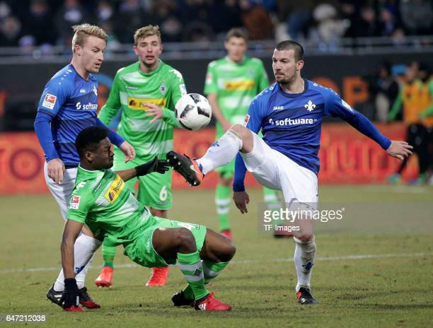 Fabian Holland of Darmstadt and BaMuaka Simakala of Gladbach and Jerome Gondorf of Darmstadt battle for the ball during the Bundesliga match between...