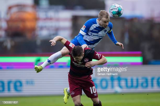Fabian Holland of Darmstadt jumps for a header with Nikola Dovedan of Nuernberg during the Second Bundesliga match between SV Darmstadt 98 and 1. FC...