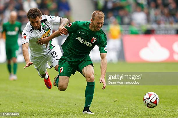 Fabian Johnson of Borussia Moenchengladbach and Ragnar Klavan of FC Augsburg battle for the ball during the Bundesliga match between Borussia...