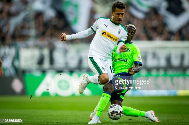 Fabian Johnson of Borussia Moenchengladbach is chased by Hamza Mendyl of FC Schalke 04 during the Bundesliga match between Borussia Moenchengladbach...