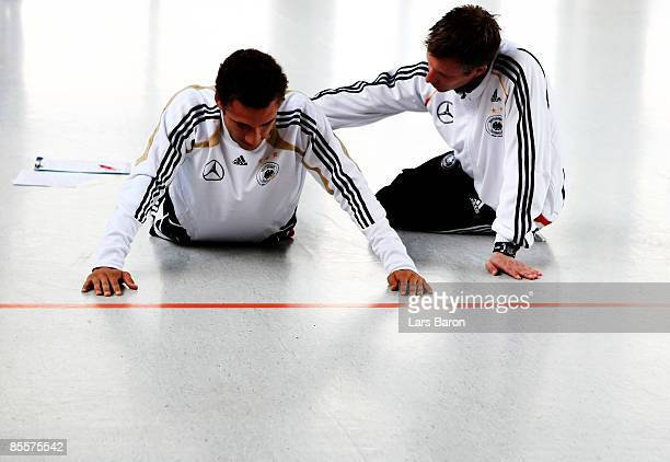 Fabian Johnson streches next to fitness Axel Burenkell during the U21 German national team fitness test at the Sportschule Kaiserau on March 24 2009...