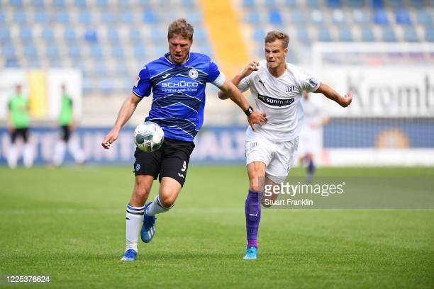 Fabian Klos of Bielefeld is challenged by Joost van Aken of Osnabrück during the Second Bundesliga match between DSC Arminia Bielefeld and VfL...