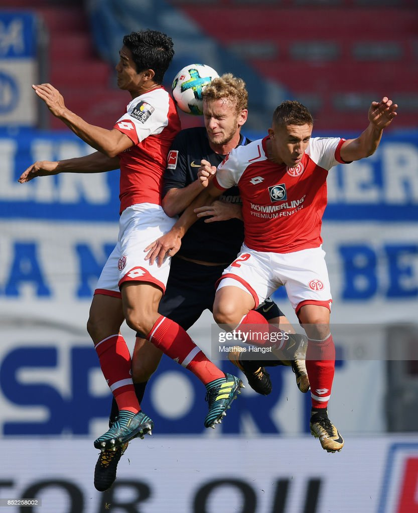 Fabian Lustenberger (C) of Berlin jumps for a header with Yoshinori Muto of Mainz and Pablo de Blasis of Mainz during the Bundesliga match between 1. FSV Mainz 05 and Hertha BSC at Opel Arena on September 23, 2017 in Mainz, Germany.