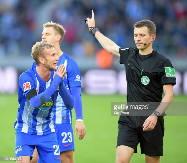 Fabian Lustenberger of Hertha BSC and referee Benjamin Cortuz during the game between Hertha BSC and SC Freiburg at the Olympiastadion on october 21...