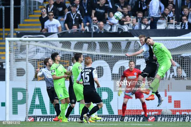 Fabian Menig of Aalen and Dustin Bomheuer of Duisburg jump for a header during during the third league match between VfR Aalen and MSV Duisburg at...