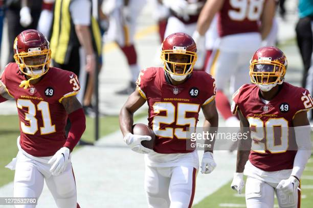 Fabian Moreau of the Washington Football Team celebrates with teammates after intercepting a pass in the second quarter against the Philadelphia...