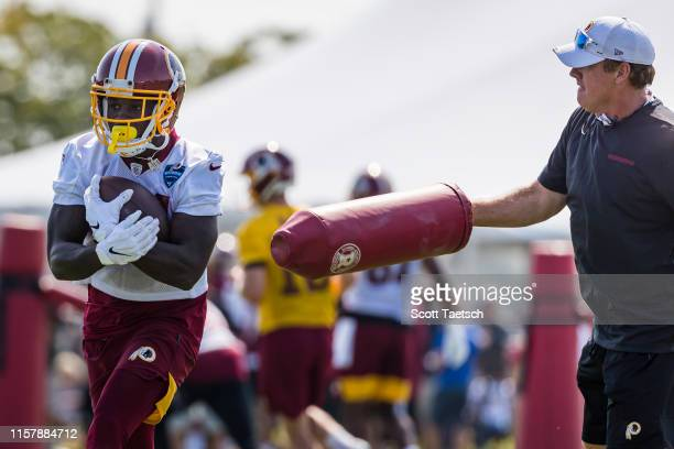 Fabian Moreau of the Washington Redskins runs with the ball as head coach Jay Gruden defends with a pad during training camp at Bon Secours...