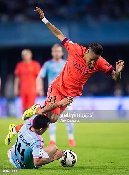 Fabian Orellana of Celta Vigo tackles Neymar Santos Jr of FC Barcelona during the La Liga match between Celta Vigo and FC Barcelona at Estadio...
