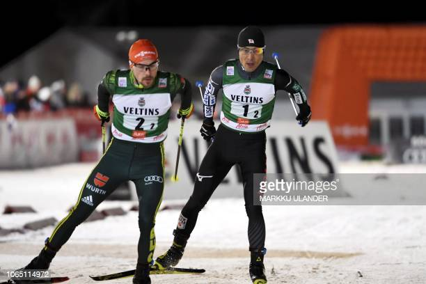 Fabian Riessle of Germany and Yoshito Watabe of Japan compete during the Men's Nordic Combined Team Competition at FIS Nordic Skiing World Cup in...