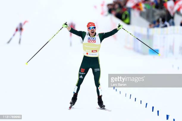 Fabian Riessle of Germany celebrates as he approaches the finish line to win Team Sprint Large Hill / 2 X 75km alongside Eric Frenzel of Germany for...