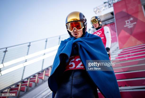 Fabian Riessle of Germany tries to keep warm at the Normal Hill during the Nordic Combined Individual Gundersen NH/10km official training on February...