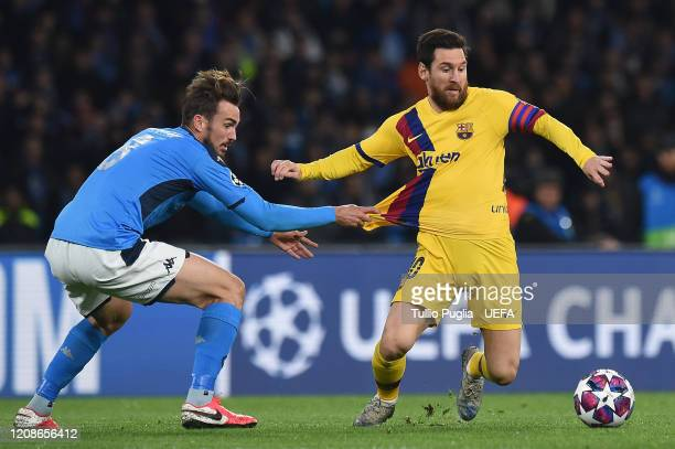Fabian Ruiz of Napoli and Lionel Messi of Barcelona compete for the ball during the UEFA Champions League round of 16 first leg match between SSC...