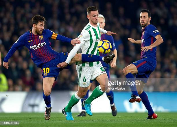 Fabian Ruiz of Real Betis Balompie competes for the ball with Lionel Messi of FC Barcelona and Sergio Busquets of FC Barcelona during the La Liga...