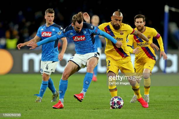 Fabian Ruiz of SSC Napoli and Arturo Vidal of FC Barcelona battle for the ball during the UEFA Champions League round of 16 first leg match between...