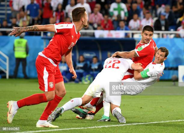 Fabian Schaer of Switzerland Aleksandar Mitrovic of Serbia and Stephan Lichtsteiner of Switzerland collide inside the Switzerland penalty area during...