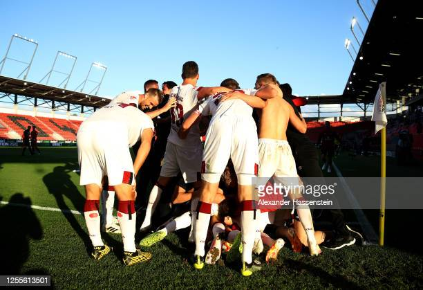 Fabian Schleusener of Nuremberg celebrates with team mates after scoring his teams first goal during the 2. Bundesliga playoff second leg match...