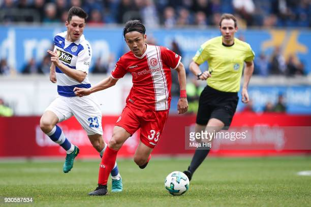 Fabian Schnellhardt of MSV Duisburg and Takashi Usami of Fortuna Duesseldorf battle for the ball during the Second Bundesliga match between MSV...