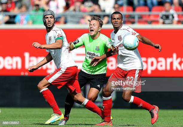 Fabian Stenzel of Chemnitz is attacked by Klaus Gjasula and Marvin Ajani of Halle during the Third League match between Hallescher FC and Chemnitzer...