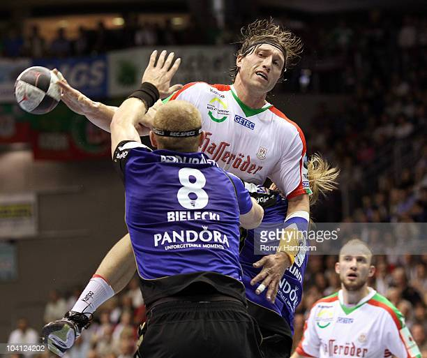 Fabian van Olphen of Magdeburg is challenged by Karol Bielecki and Borge Lund of Rhein Neckar Loewen during the Toyota Handball Bundesliga match...