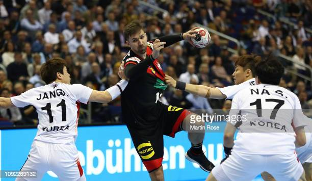 Fabian Weide of Germany is challenged by DongHyung Jang of Korea during the 26th IHF Men's World Championship group A match between Korea and Germany...