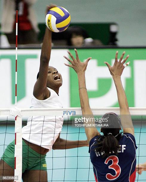 Fabiana Claudino of Brazil spikes the ball as Tayyiba Haneef of the US tries to block during their round robin match in the 2005 World Grand Champion...