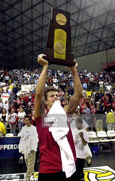 Fabiano Barreto of Lewis University hoists championship trophy after 4244 3027 3021 2330 1512 victory over Brigham Young in the NCAA men's volleyball...