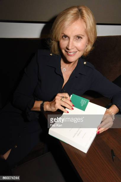 Fabienne Amiach poses with her new book during Olivier Michel Private Dinner Party at Sens Uniques Restaurant on October 10 2017 in Paris France r