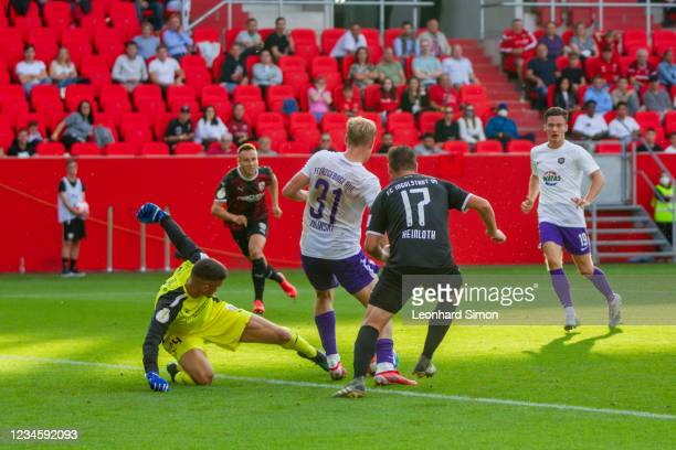 Fabijan Bunti and Michael Heinloth of FC Ingolstadt 04 and Ben Zolinski of Erzgebirge Aue in action during the DFB Cup first round match between FC...