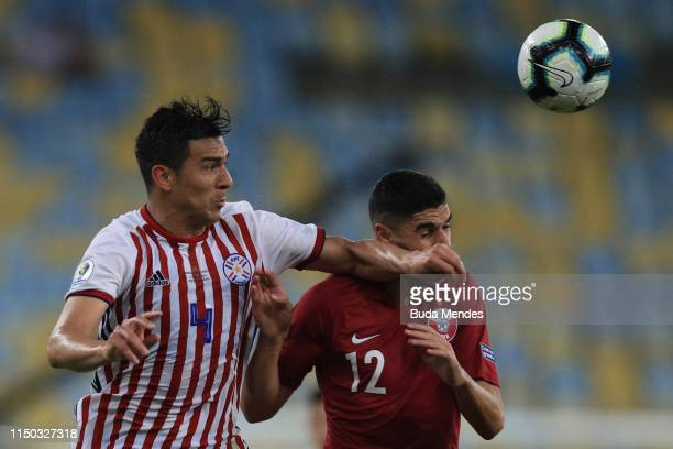 Fabián Balbuena of Paraguay and Karim Boudiaf of Qatar compete for the ball during the Copa America Brazil 2019 group B match between Paraguay and...