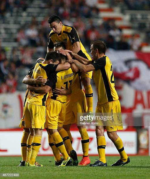 Fabián Estoyanoff of Peñarol celebrates with teammates after scoring the first goal of his team during a match between Estudiantes and Peñarol as...