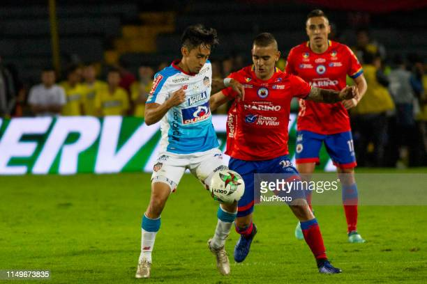 Fabián Sambueza of Junior fights the ball against Jown Cardona of Deportivo Pasto during the final second leg match between Deportivo Pasto and...