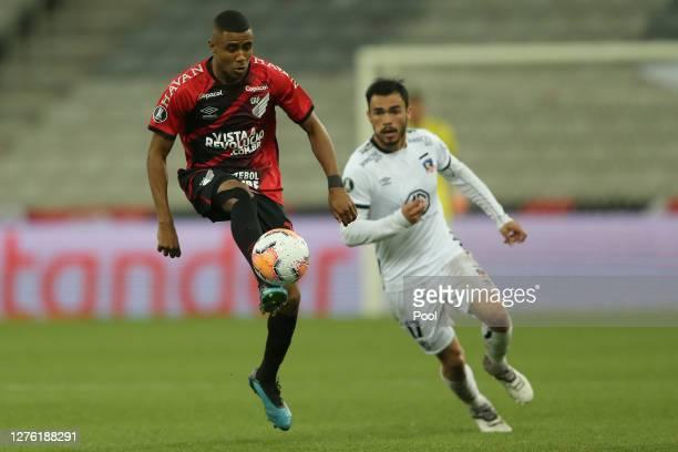 Fabinho of Athletico Paranaense controls the ball past Juan Manuel Insaurralde of ColoColo during a group C match of Copa CONMEBOL Libertadores 2020...